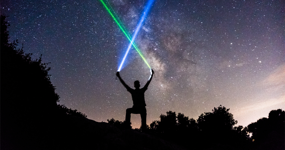 night sky with silhouette of person holding a light saber