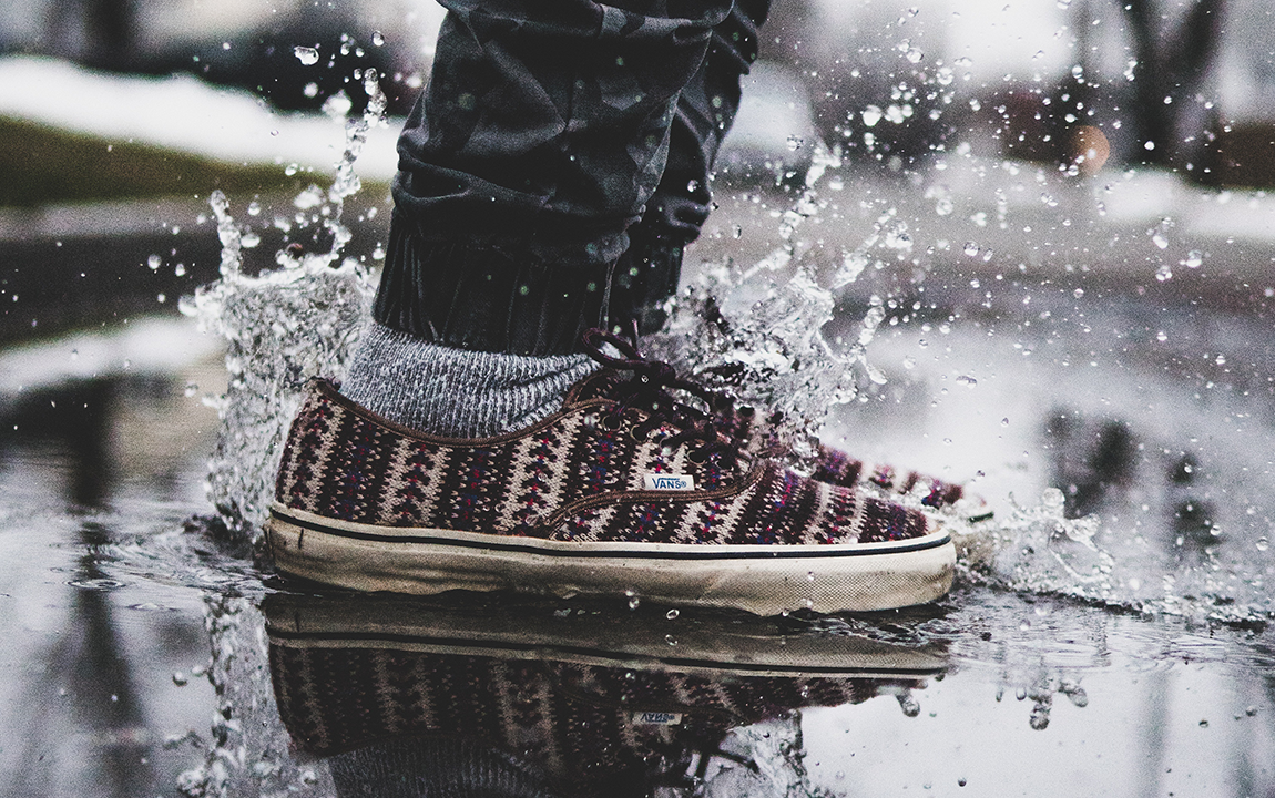 person jumping into a puddle (you can only see the shoes)