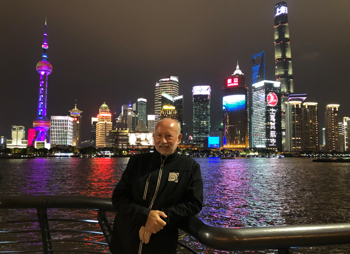 Blog author John Larmer standing in front of the city night skyline in China