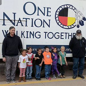 group picture of students and teachers in front of the sign One Nation Walking Together