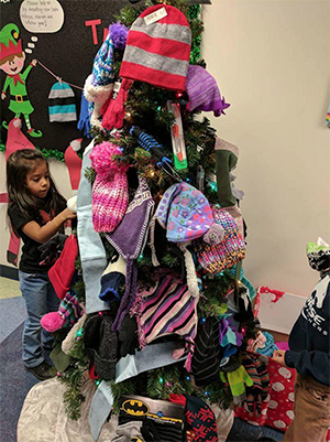 a child putting hats on a christmas tree for her pbl project
