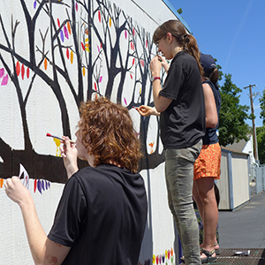 students painting a tree on a building wall