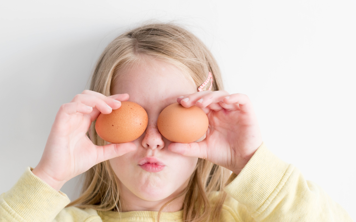 girl holding eggs to her face like eyes