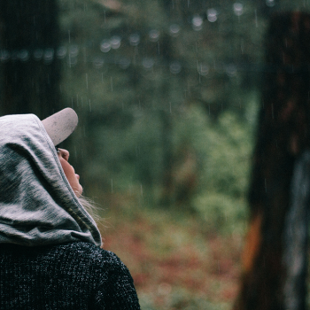 woman looking at the rain in the forest