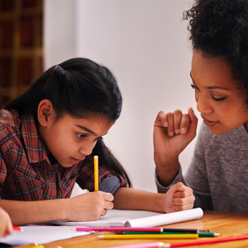 elementary student doing schoolwork with parent